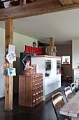 Vintage Schubladenschrank neben moderner Küchenkombination in renoviertem Landhausambiente