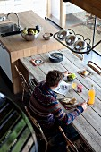Man sitting at rustic wooden table eating breakfast in renovated country house