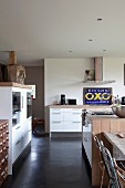 Open-plan kitchen with modern cupboard elements and fitted appliances in renovated country house belonging to artist