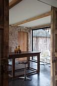 Vintage Barhocker vor schlichter Holztheke in renoviertem Landhaus mit sichtbarer Ziegelwand