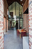 Dining area with tall brick walls and two-storey glass wall with steel frame