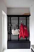 Massgefertigte Garderobe aus Lächenholz mit aufgehängter Kleidung