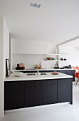 Kitchen counter with dark base units and white worksurface in contemporary kitchen