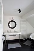 Retro Waschtisch mit Metallfüssen unter rundem Spiegel mit schwarzem Rahmen, seitlich Handtuchtrockner an Wand