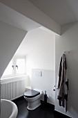 Toilette in weißem Badezimmer mit schwarzen Dielenboden unter dem Dach