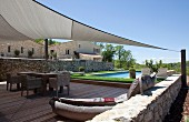 View across wooden terrace with awning and adjoining pool too traditional house in southern France