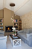 Seating area with loose-covered sofas, coffee table and fireplace flanked by fitted bookcases