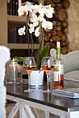 Potted white orchid, bottle and two glasses of rose wine on coffee table in elegant, country-house interior