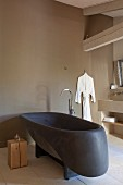 Black designer bathtub and wooden cube side table in purist bathroom