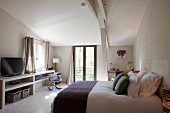 Subtle accents of colour in simple bedroom of Provençal guest house