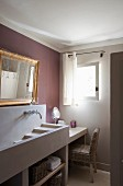Concrete cascade sink on washstand below gilt-framed mirror on wall painted mauve