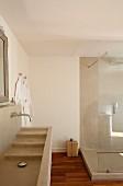 Naturtöne im Bad: Waschtisch mit Kaskadenbecken und Duschkabine aus Beton, daneben Holzklotz als Ablage