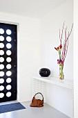 Amaryllisblüten und Zweige auf modernem weißem Konsolentisch, seitlich schwarze Haustür mit runden Glasausschnitten