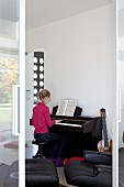 View through open sliding door of girl playing piano in music room