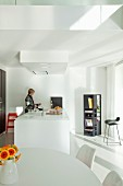 Open-plan, white designer kitchen with dining area and kitchen counter; woman in background