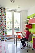 Girl seated at desk in front of French windows with floor-length, multicoloured, polka-dot curtains in child's bedroom