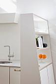 Asymmetrischer weißer Küchenschrank mit offenem Regal an Designerküchenzeile mit Carraramarmor-Küchenarbeitsplatte