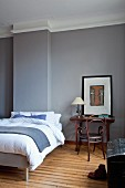 Double bed with pale bed linen next to table and wooden Thonet armchair in grey-painted bedroom