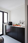 Minimalist kitchen counter with black doors and knives on magnetic bar on wall