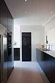 Schwarze Designerküche mit heller Arbeitsfläche und raumhoher Schrankzone mit Einbaugeräten, Notizen an Tür mit dunkler Tafelfarbe