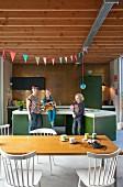 Offene Wohnküche mit Mutter und zwei Kindern an Kochinsel; vorne Esstisch mit Stühlen