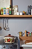 Retro saucepan on gas cooker below spices on narrow shelf