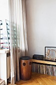 Vintage wooden speakers, record collection below sideboard in corner and glass display case of toy cars on windowsill behind curtain