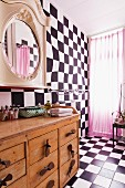 Chequered floor and wall, pink curtain on window and rustic, wooden chest of drawers