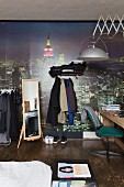 Teenager's bedroom with desk, clothes racks and cityscape mural wallpaper