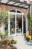 View from garden onto gravel terrace adjoining house with arched terrace doors and windows in brick facade