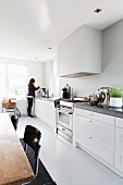 White kitchen counter along entire wall, extractor hood, dining area and woman in background