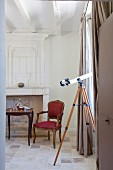 Telescope at window with floor-length curtains, antique chair and Rococo-style side table in front of fireplace