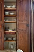 Holzschrank mit offener Tür und Blick auf Geschirr