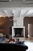 Rustic interior with open fireplace, comfortable sofa, wall painted dark brown and white, wood-beamed ceiling