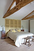 Double bed with white bedspread in front of closed shutters in renovated attic bedroom with exposed wooden roof structure