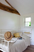 Antique, white bed in renovated attic bedroom