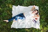 Overhead portrait of woman lying on picnic blanket in park