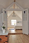 Open, lattice double doors in simple, white, country-house interior in attic with plain wooden floors and Scandinavian, vintage-style ambiance