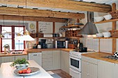 Scandinavian, vintage-style, country-house kitchen with wooden kitchen worksurfaces, wall-mounted shelves and rustic wood-beamed ceilings