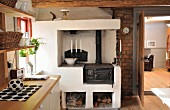 Vintage wood-fired cooker with masonry surround and firewood in niches against brick wall