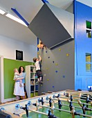 Mother and children in playroom with climbing wall and table football set in foreground