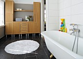 Colourful bathtub toy on free-standing bathtub with retro tap fittings; cabinets with integrated shelves in background