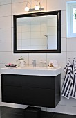 Washstand with black base unit mounted on white tiled wall below framed, illuminated mirror