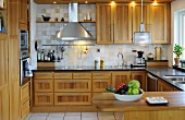 Contemporary fitted kitchen and wooden fronts and rod-shaped handles