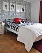Bedroom with black and white artworks on wall with paisley wallpaper and double bed with black and white gingham bedspread