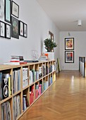 Gallery of pictures above books and records in sideboard compartments running along corridor; herringbone parquet floor