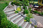 Terraced, gravel steps supported by boulders and with wooden edges in front of seating area on wooden decking