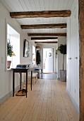 Gangbereich in renoviertem, Holzhaus mit weisser Verschalung und Deckenbalken