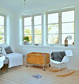 White, designer rocking chair and vintage toy box on castors in minimalist, Scandinavian interior