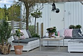 Comfortable seating area with DIY outdoor furniture on Scandinavian-style terrace